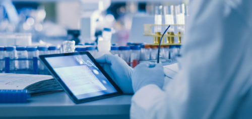 Senior Male Research Scientist is Using a Tablet Computer in a Modern High-Tech Laboratory. Genetics and Pharmaceutical Studies and Researches.